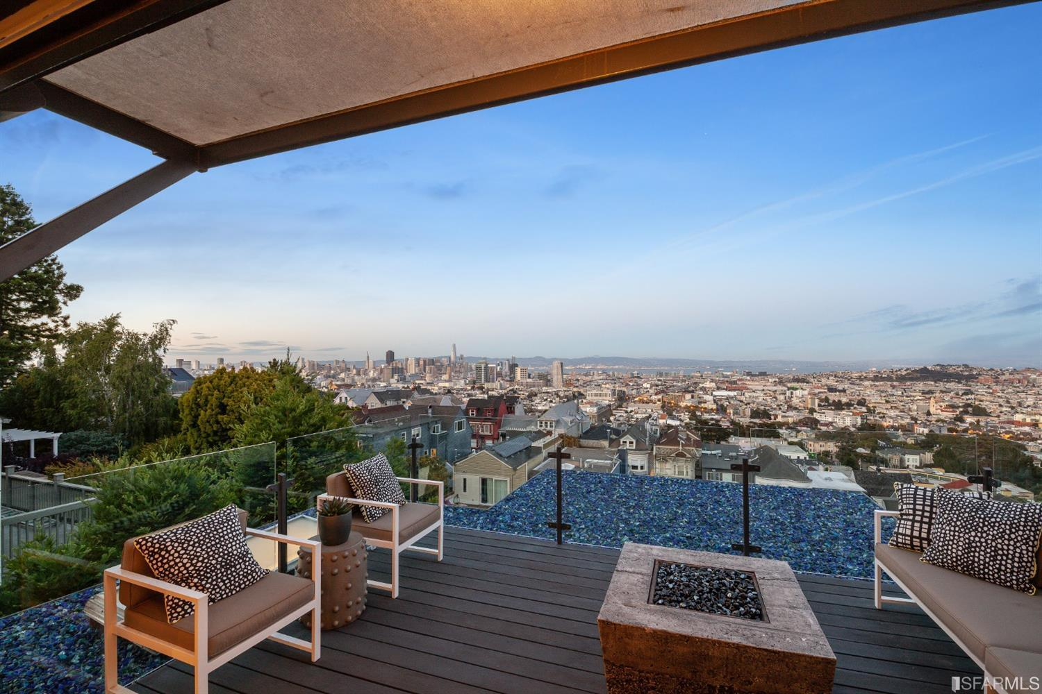 Balcony with modern outdoor furniture and a firepit overlooking the city