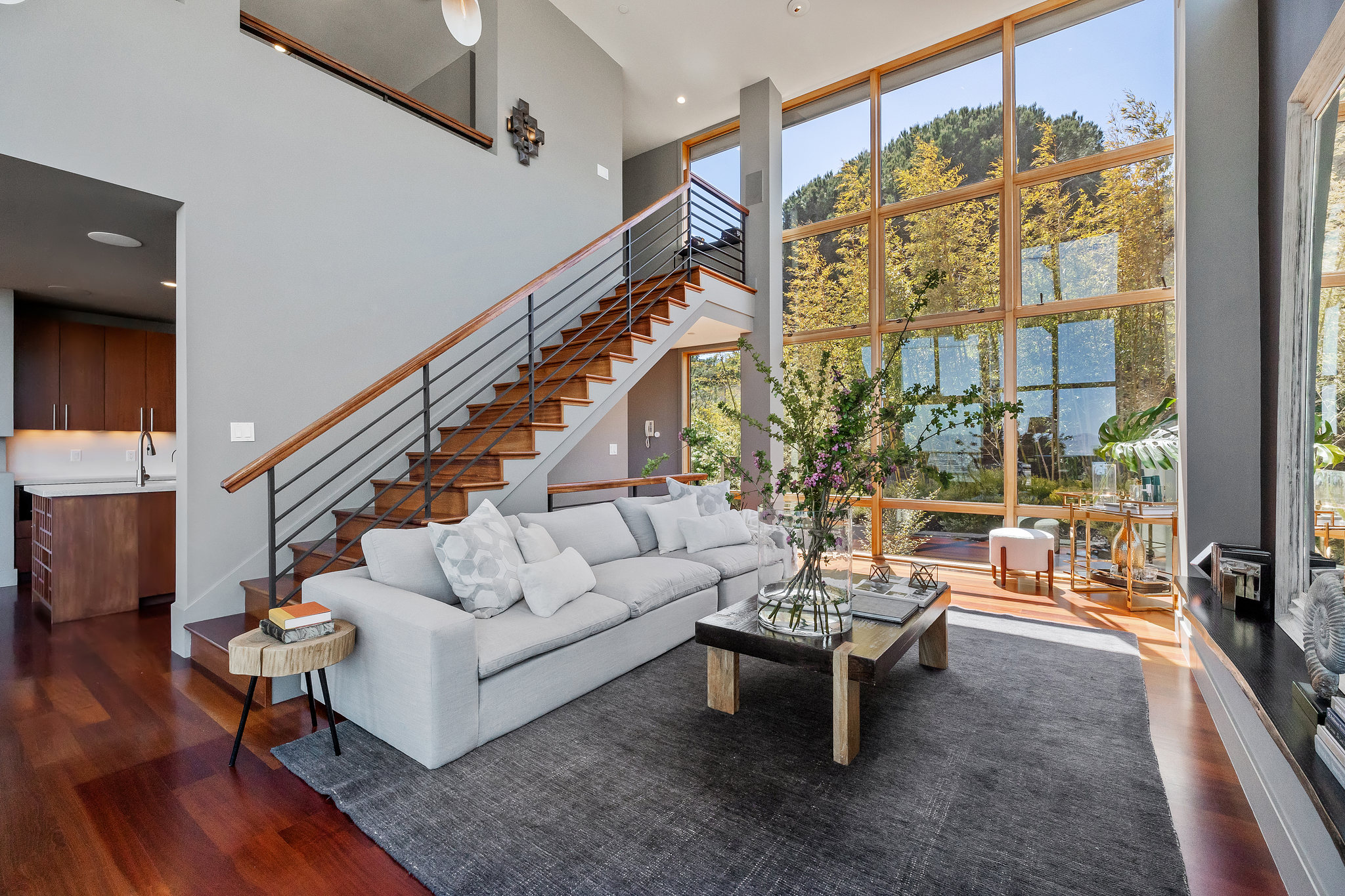 Peaceful morning image of living room with white couch, large mirror, and floor to ceiling windows