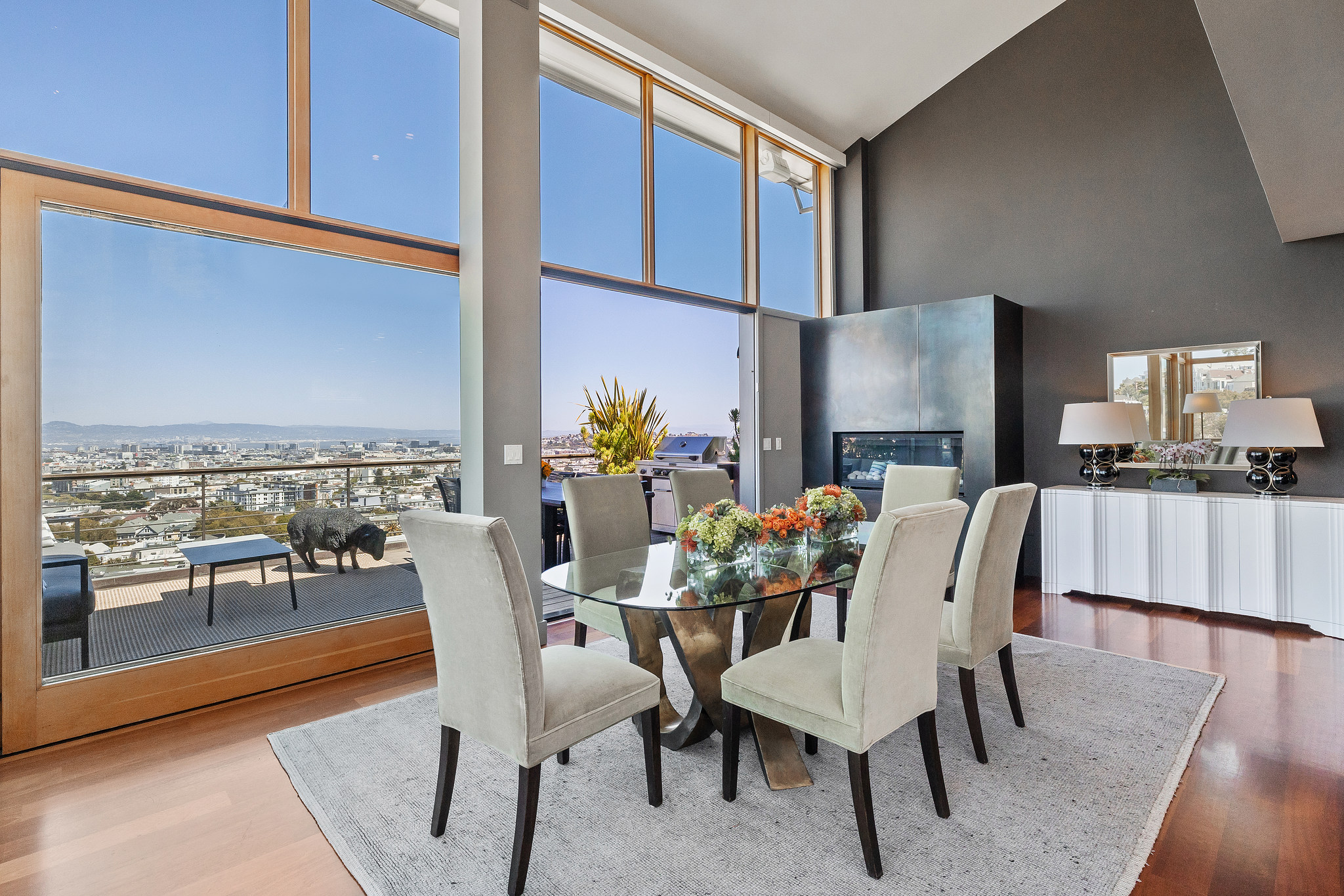 Dining room table set overlooking city through large windows