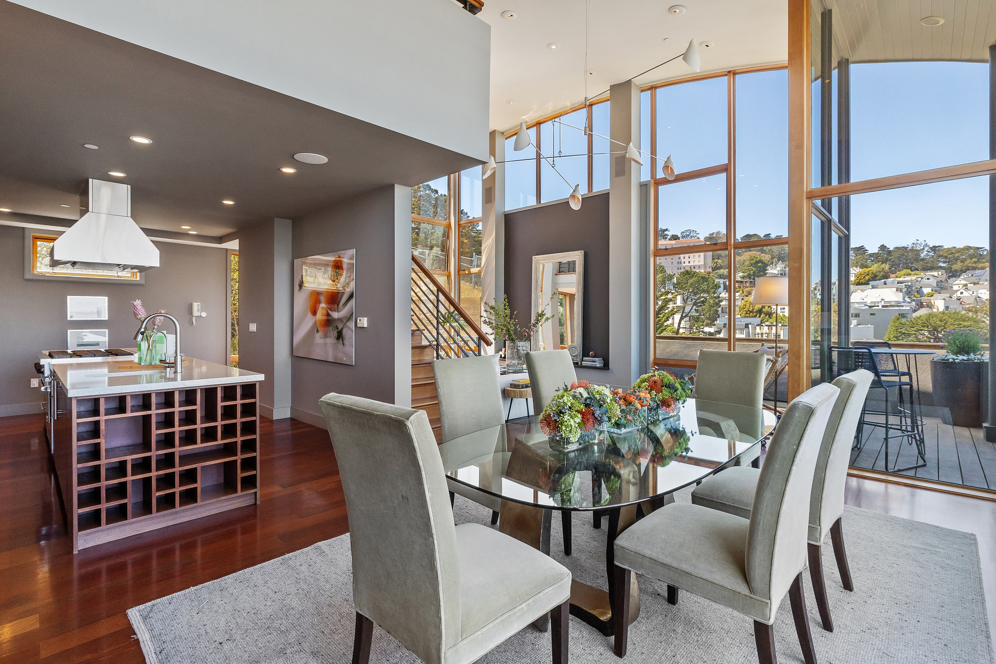 Dining room set with view of modern kitchen behind it