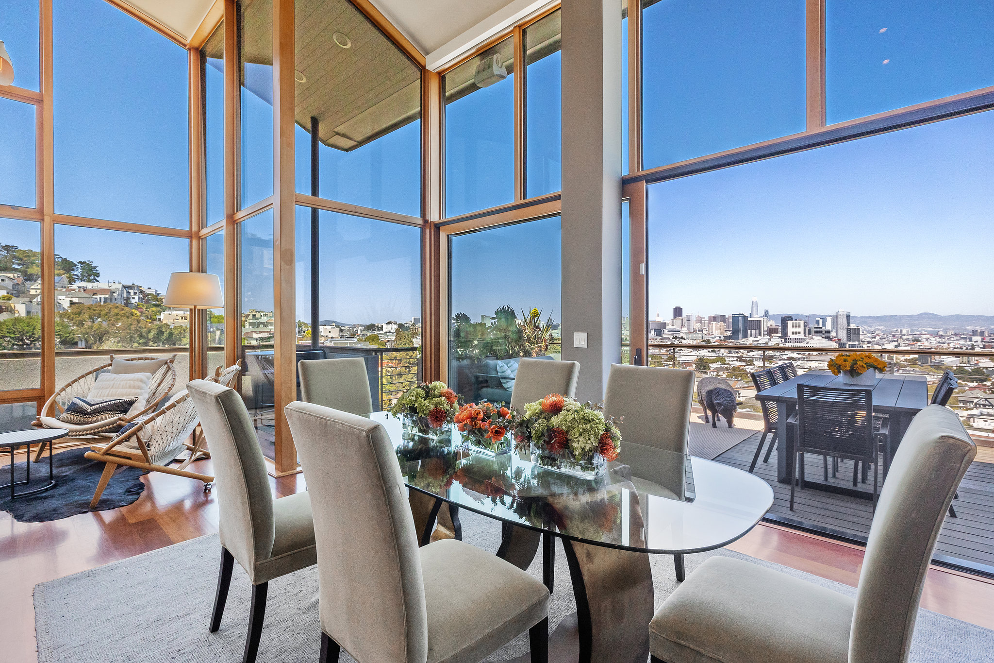 Dining room table surrounded by floor to ceiling windows with natural light coming in