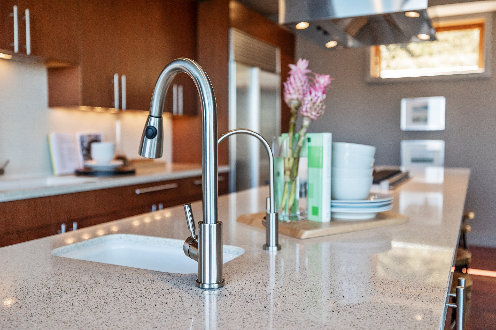 Up close image of small sink in kitchen with granite countertops and wood cabinets