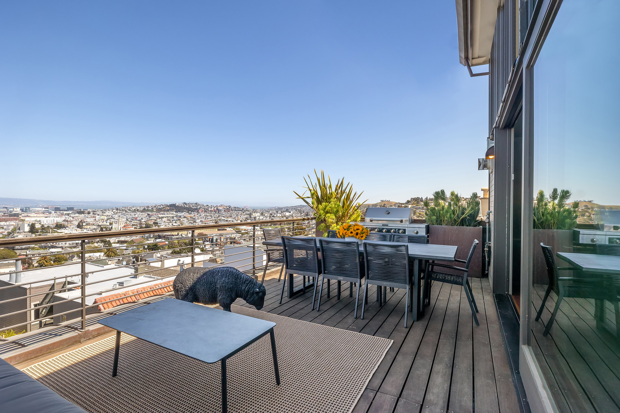 Outdoor furniture on balcony overlooking city during the day