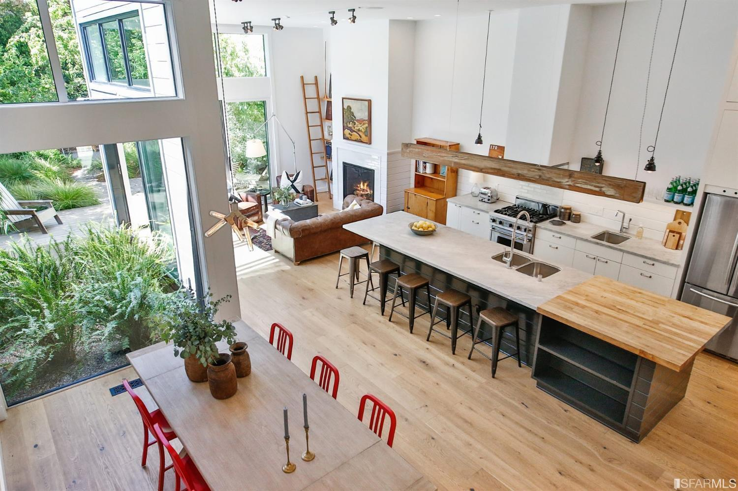 Aerial view of chic white kitchen and living room with floor to ceiling windows