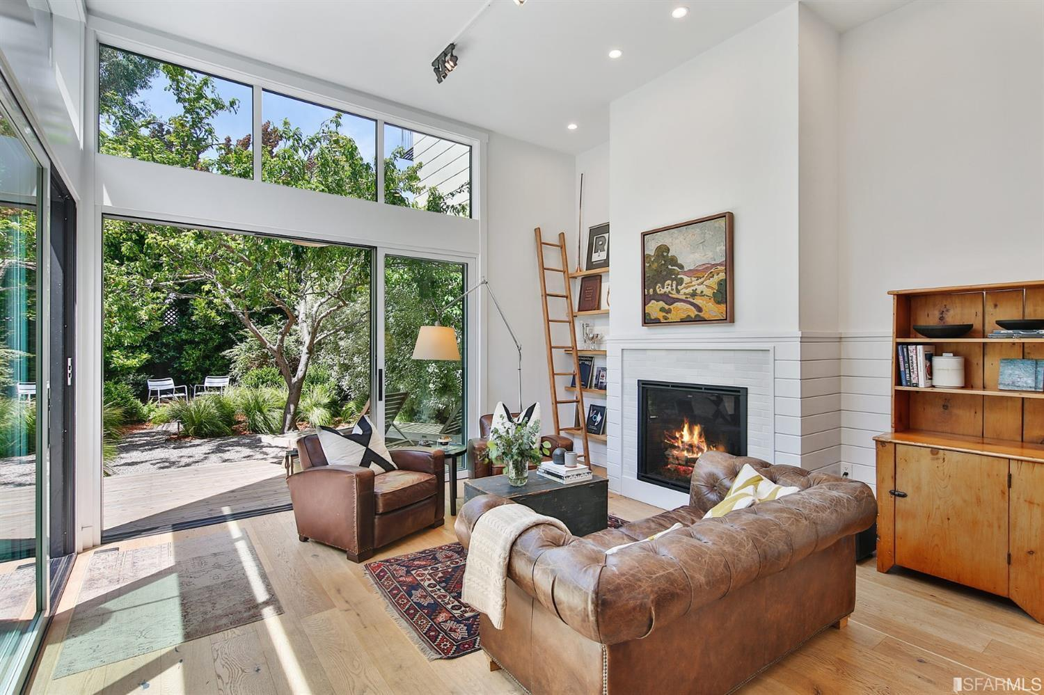 Brown couch set in living room area with fireplace and large floor to ceiling windows