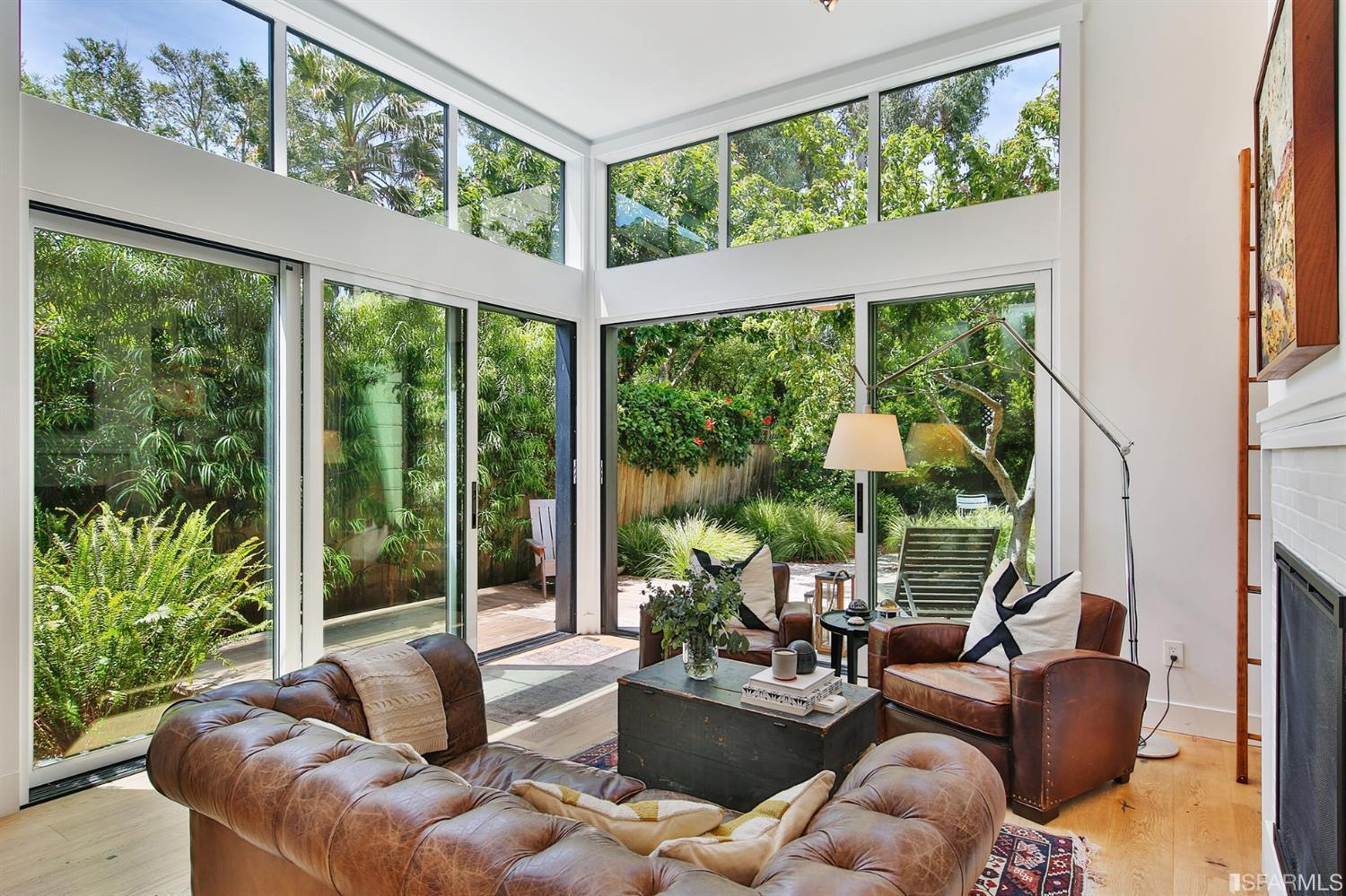Brown couch set in living room area with large floor to ceiling windows