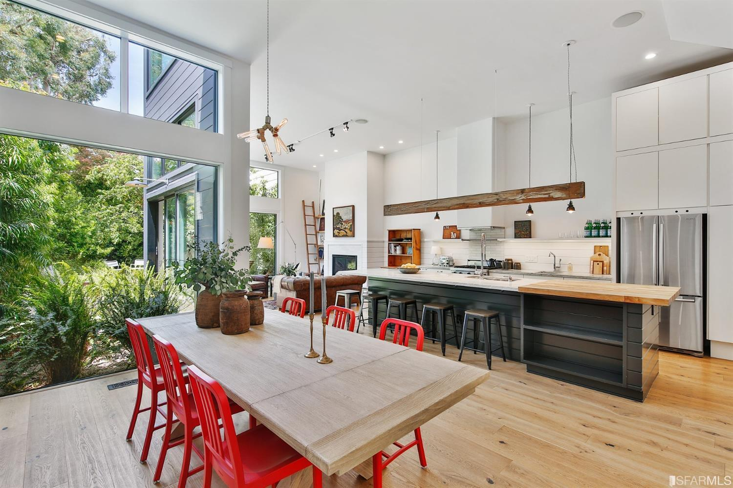 Dining table with red chairs off a chic white and wood kitchen