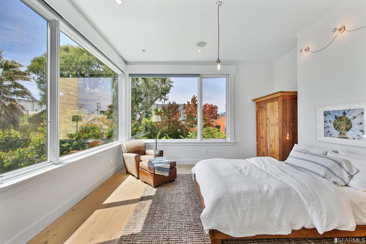Bedroom with large windows letting in lots of natural sunlight