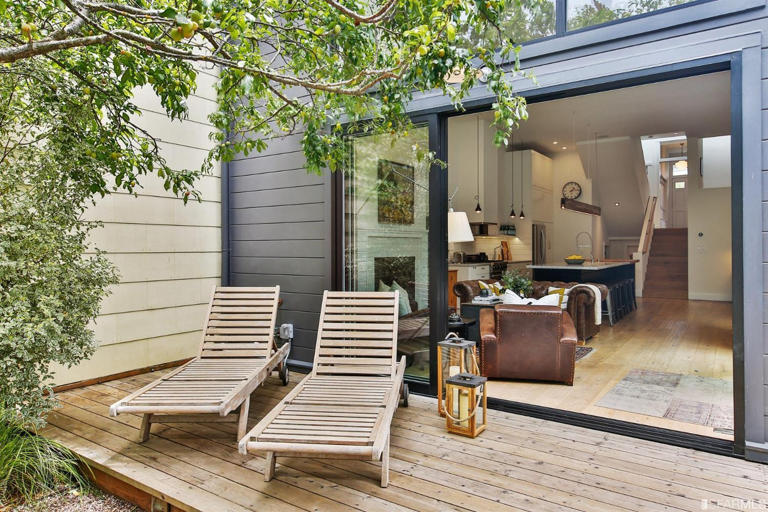 Two lounge chairs on back patio off the back of modern house