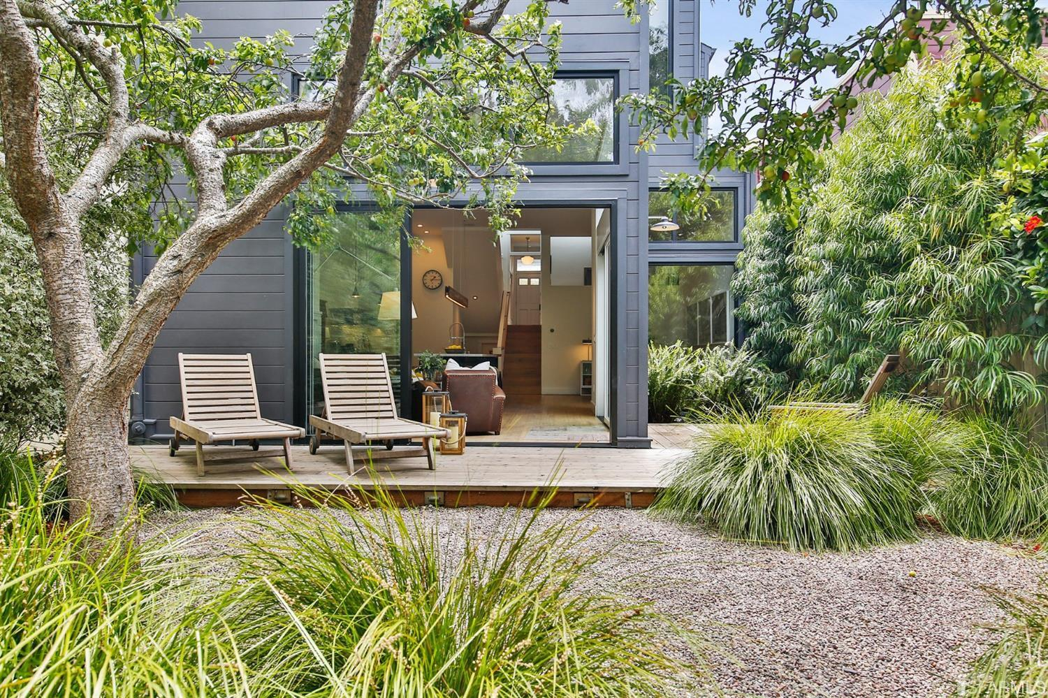 Two lounge chairs on outdoor patio surrounded by greenery